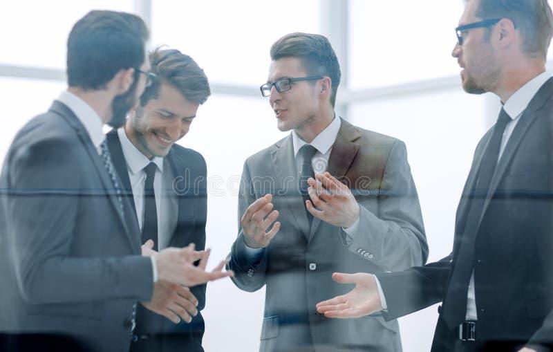 Команда дела обсуждает что-то стоя в офисе стоковое фото rf