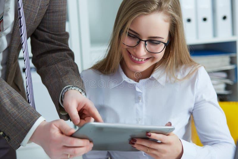 Команда дела работая на столе офиса и используя цифровую таблетку экрана касания стоковое изображение