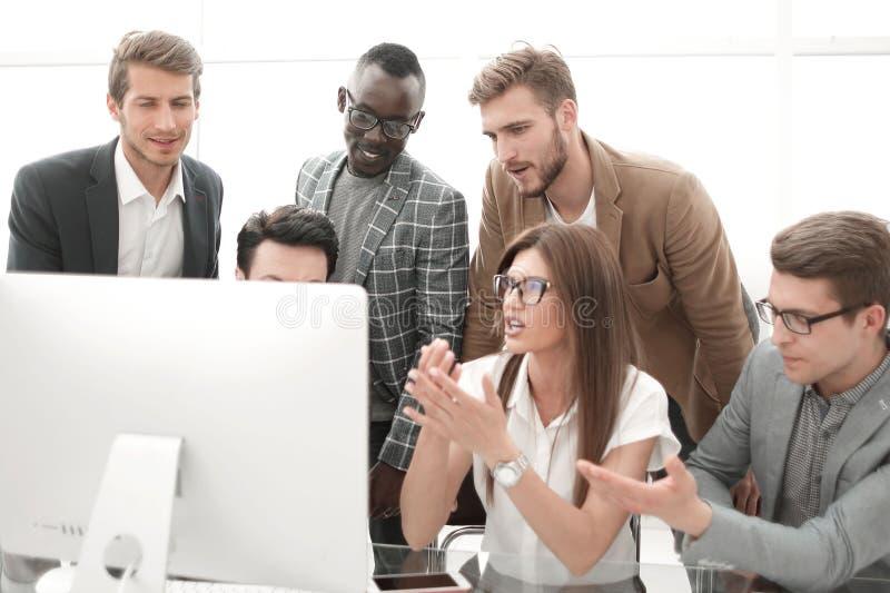Команда дела смотря монитор настольного компьютера ждет онлайн результат стоковое фото rf