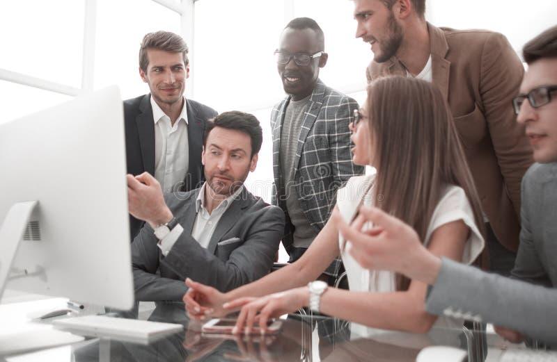 Команда дела смотря монитор настольного компьютера ждет онлайн результат стоковое изображение rf