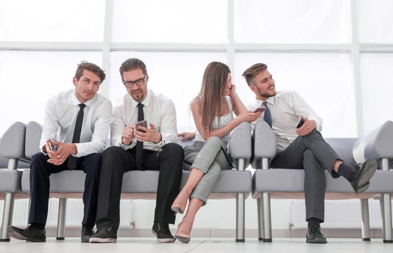 Команда дела с мобильными телефонами сидя в лобби офиса стоковые изображения rf