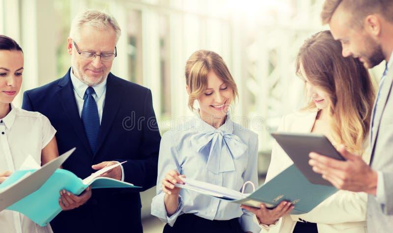 Команда дела с ПК планшета и папки на офисе стоковая фотография