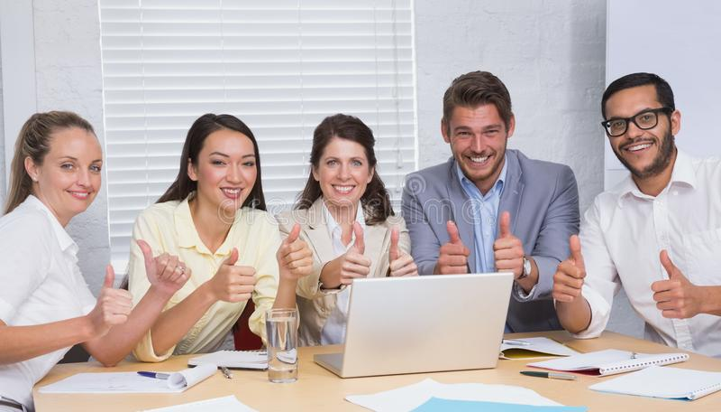 Команда дела усмехаясь на камере показывая большие пальцы руки вверх стоковое фото rf
