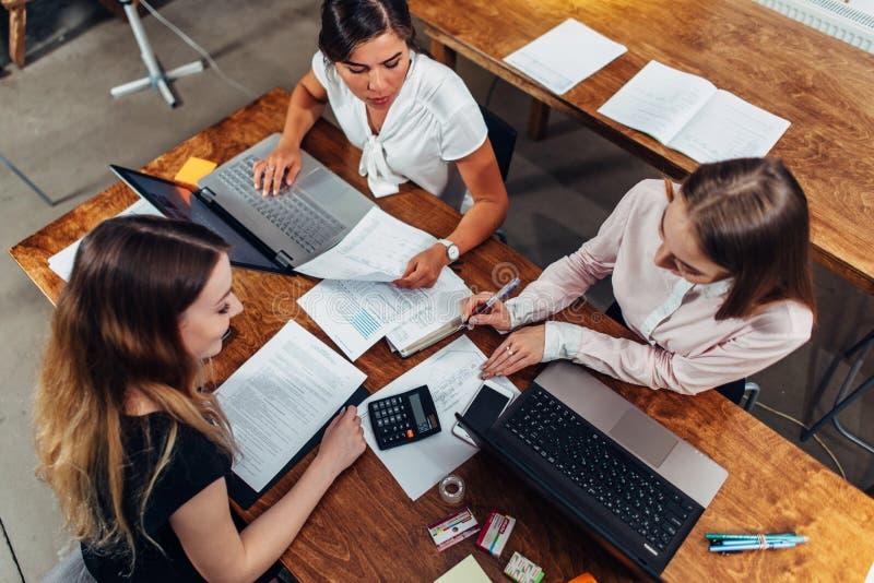 Команда женских бухгалтеров подготавливая ежегодный финансовый отчет работая с бумагами используя компьтер-книжки сидя на столе в стоковые изображения