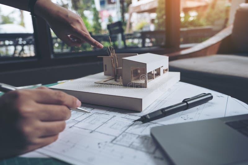 Команда коллеги архитекторов обсуждая и указывая на массовую модель с рисовальной бумагой магазина стоковая фотография rf
