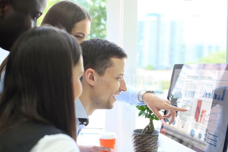 Команда коллег коллективно обсуждать совместно пока работающ на компьютере стоковые изображения