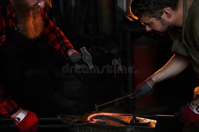 Команда кузнецов формируя heated металл стоковое фото rf