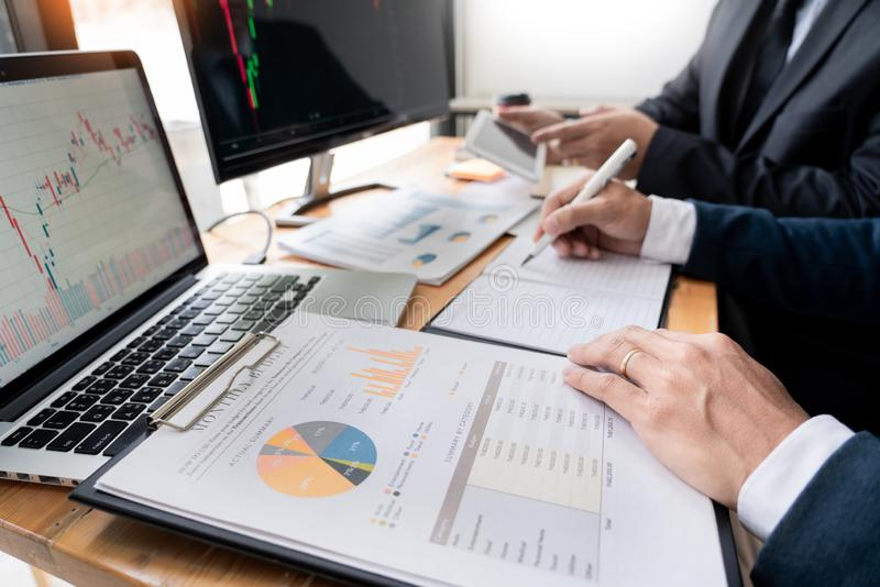 Команда маклеров обсуждая с экранами дисплея анализируя данные, диаграммы и отчеты торговой операции фондовой биржи для вклада стоковое фото
