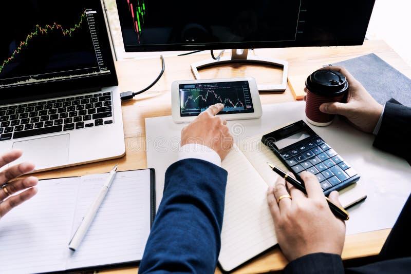 Команда маклеров обсуждая с экранами дисплея анализируя данные, диаграммы и отчеты торговой операции фондовой биржи для вклада стоковые изображения