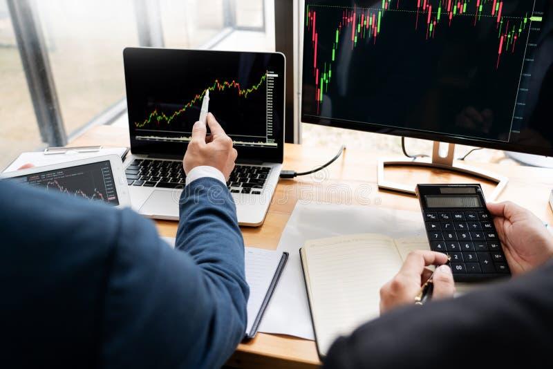 Команда маклеров обсуждая с экранами дисплея анализируя данные, диаграммы и отчеты торговой операции фондовой биржи для вклада стоковая фотография rf