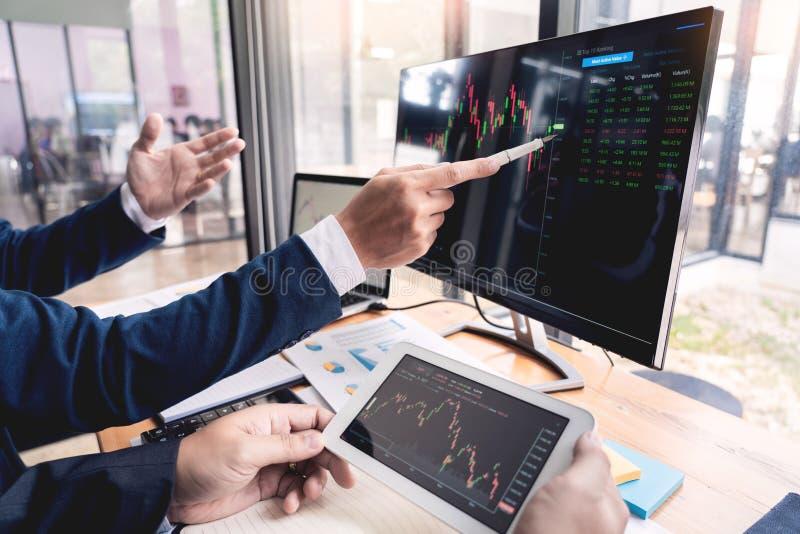 Команда маклеров обсуждая с экранами дисплея анализируя данные, диаграммы и отчеты торговой операции фондовой биржи для вклада стоковое изображение
