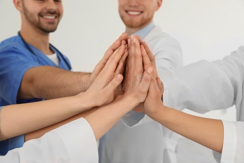Команда медицинских работников держа руки совместно на светлой предпосылке Концепция единства стоковое фото rf