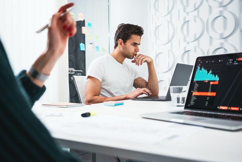 Команда менеджеров бизнесмена и женщины сидя на настольной и контролируя статистике на ноутбуке экрана стоковые фото