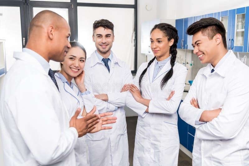 Команда молодых докторов в пальто лаборатории обсуждая работу стоковые изображения rf