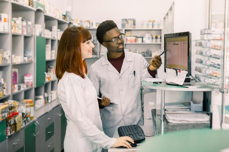 Команда 2 молодых apothecaries в фармации стоя перед полками с лекарствами и работая на компьютере делая заказ стоковые изображения