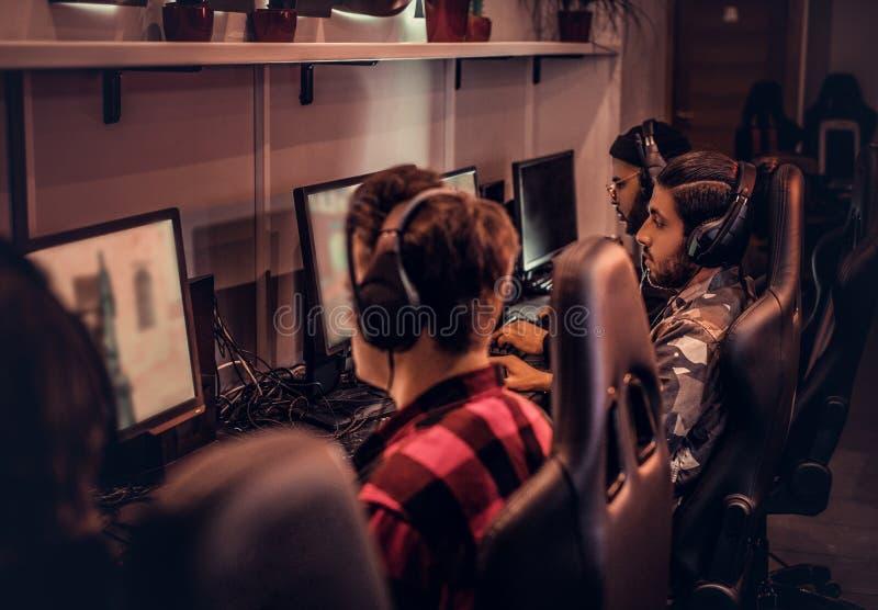 Команда подростковых gamers играет в предназначенной для многих игроков видеоигре на ПК в клубе игры стоковая фотография rf