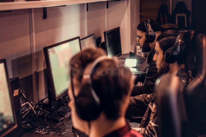 Команда подростковых gamers играет в предназначенной для многих игроков видеоигре на ПК в клубе игры стоковое изображение rf