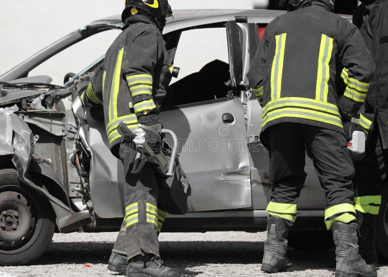 Команда пожарных с ножницами после дорожного происшествия стоковое изображение rf