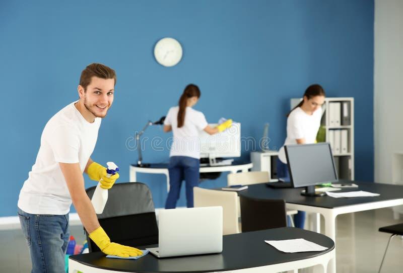 Команда привратников очищая офис стоковые фотографии rf