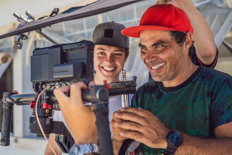 Команда продукции на коммерчески видео- всходе Оператор Steadicam использует стабилизатор и кино-степень камеры 3 осей стоковая фотография