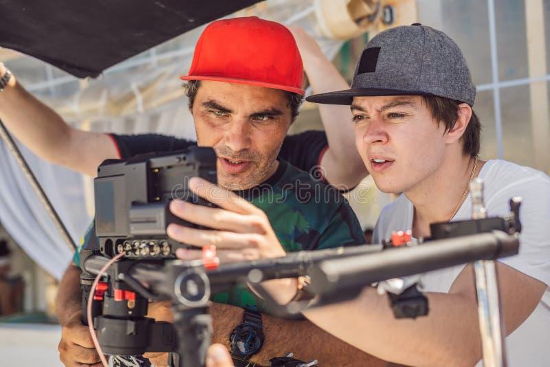 Команда продукции на коммерчески видео- всходе Оператор Steadicam использует стабилизатор и кино-степень камеры 3 осей стоковые фото
