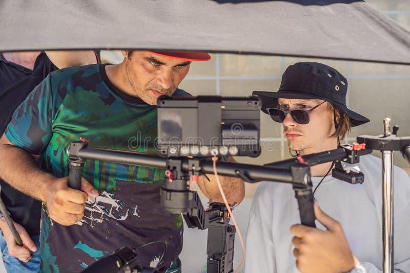 Команда продукции на коммерчески видео- всходе Оператор Steadicam использует стабилизатор и кино-степень камеры 3 осей стоковое изображение rf