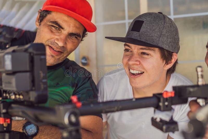 Команда продукции на коммерчески видео- всходе Оператор Steadicam использует стабилизатор и кино-степень камеры 3 осей стоковое фото