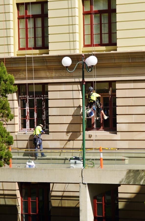 Команда промышленных художников в шестерне безопасности крася старое офисное здание стоковое фото rf