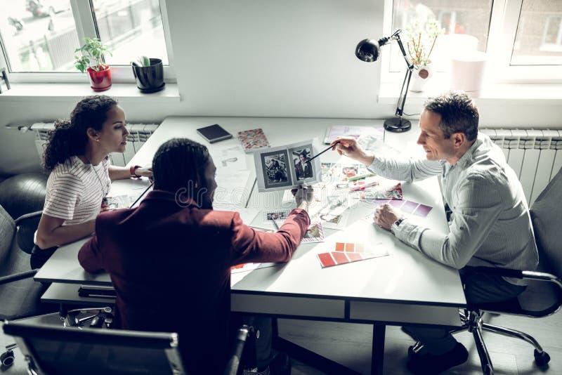 Команда работая для журнала о моде обсуждая новый выпуск стоковое фото rf