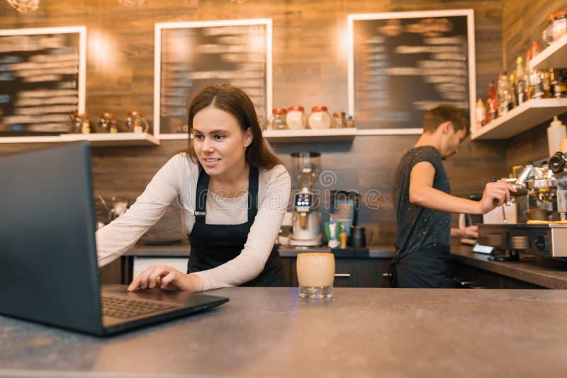 Команда работников кофейни работая около счетчика с ноутбуком и делая кофе, дело кафа стоковая фотография