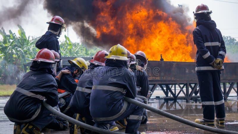 Команда тренирующих пожаротушения тушит огромный огонь с водой стоковое фото