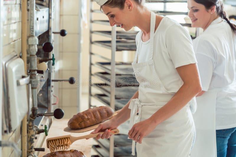 Команда 2 хлебопеков подготавливая и покрывая хлеб стоковые фотографии rf