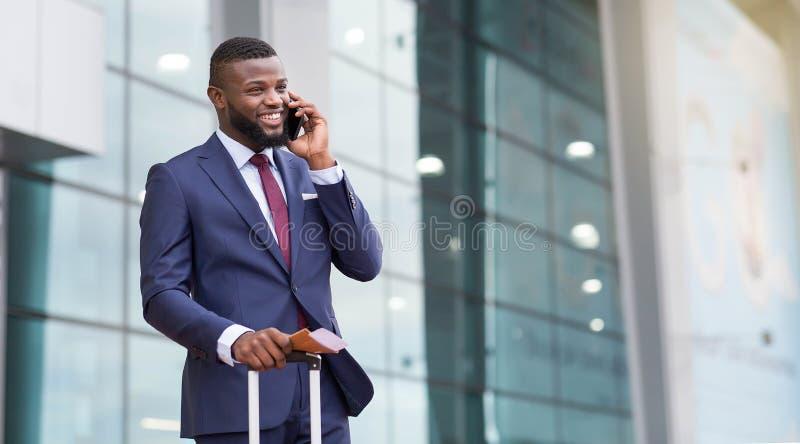Командировка Счастливый менеджер говоря по телефону и держа чемодан в аэропорте стоковые изображения rf