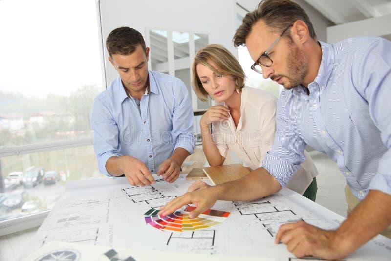 Команда архитекторов обсуждая крася дизайны стоковые фотографии rf