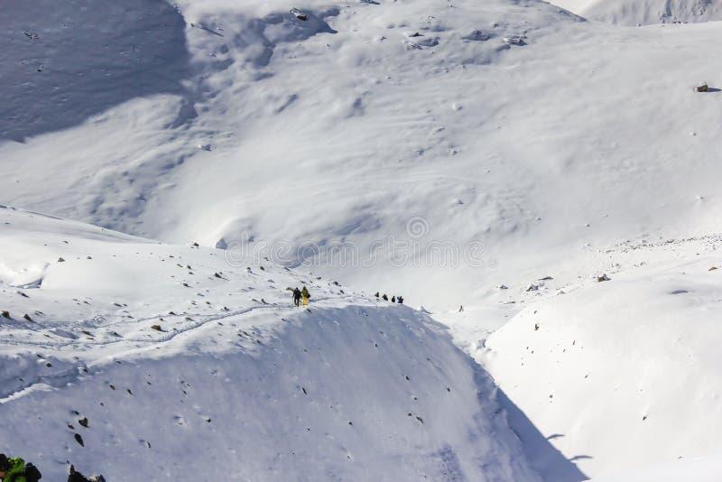 Команда альпинистов идя к саммиту с снегом и ветром стоковое изображение