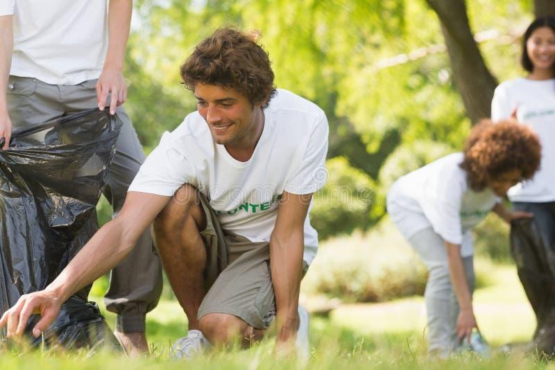 Команда волонтеров выбирая вверх сор в парке стоковые изображения