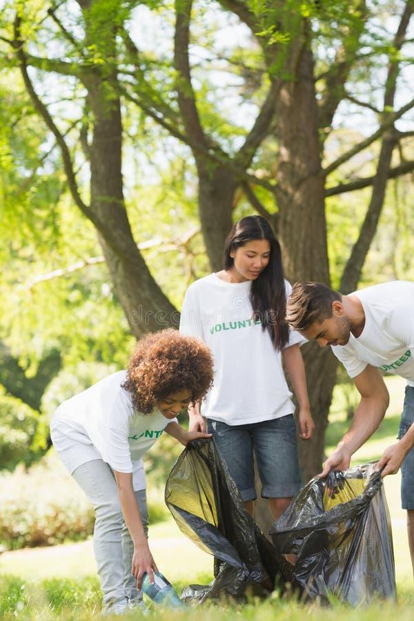 Команда волонтеров выбирая вверх сор в парке стоковая фотография