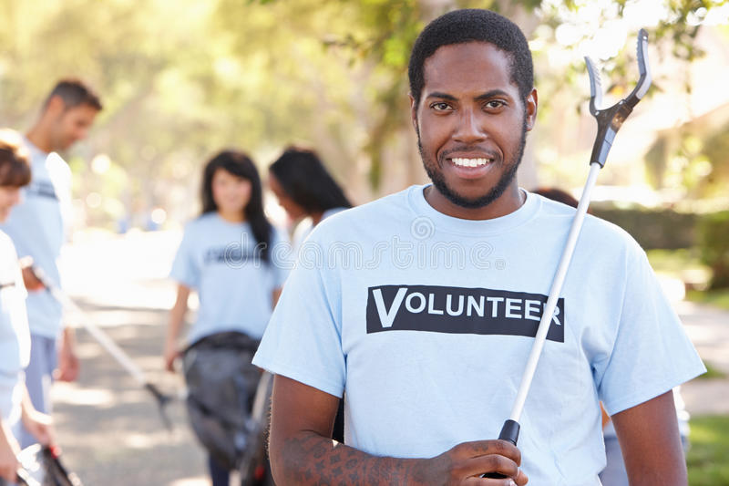Команда волонтеров выбирая вверх сор в слободской улице стоковые изображения