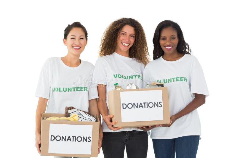 Команда волонтеров усмехаясь на камере держа коробки пожертвований стоковое изображение