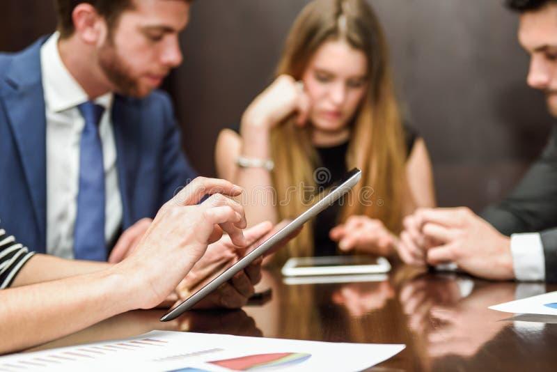 Команда дела используя планшет, который нужно работать с финансовыми данными стоковые фото