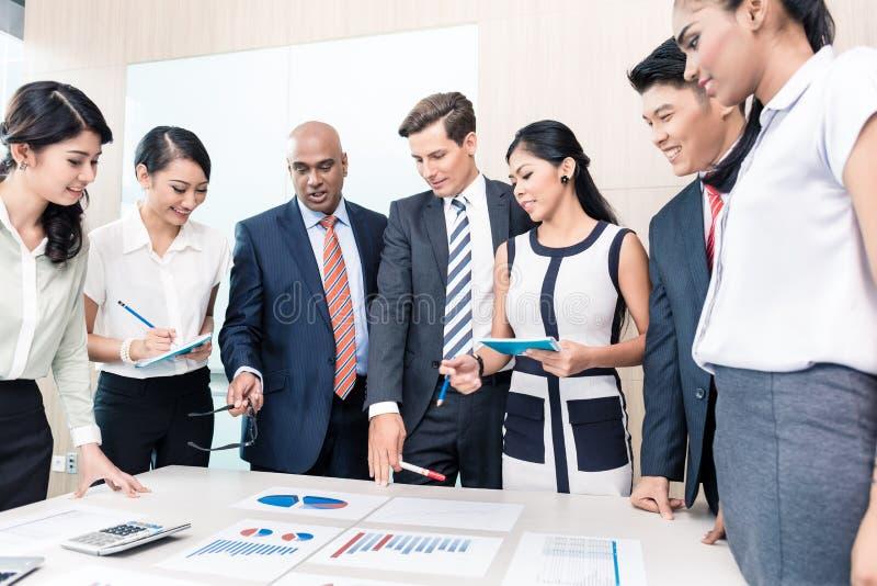 Команда дела обсуждая диаграммы и номера в встрече стоковая фотография rf
