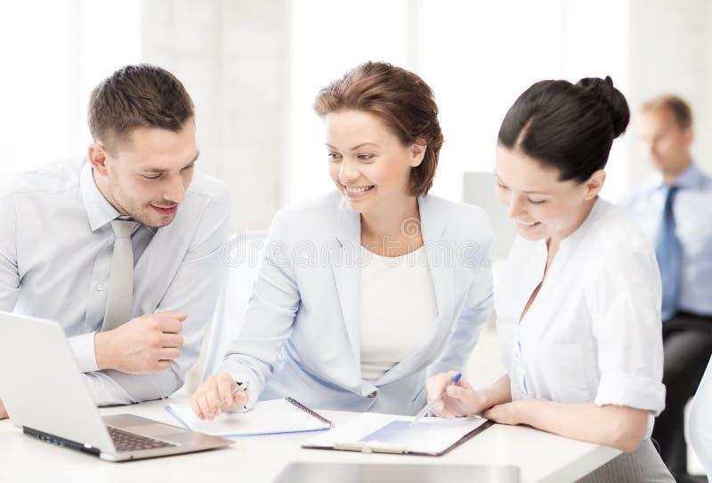 Команда дела обсуждая что-то в офисе стоковые изображения