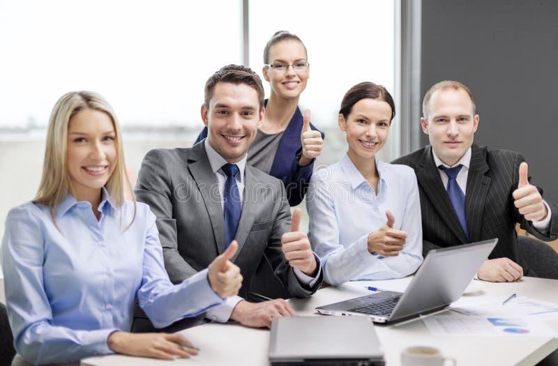 Команда дела показывая большие пальцы руки вверх в офисе стоковое изображение rf