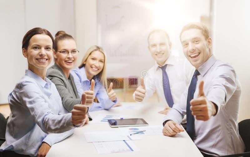 Команда дела показывая большие пальцы руки вверх в офисе стоковая фотография