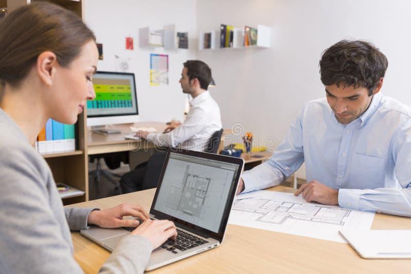 Команда дела работая на компьтер-книжке в офисе стоковая фотография rf