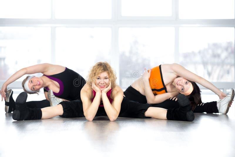 Команда 3 женщин представляя, сидя в разделениях в классе фитнеса стоковые изображения