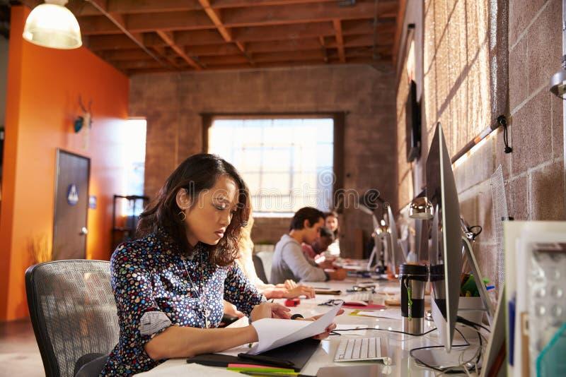 Команда дизайнеров работая на столах в современном офисе стоковое фото