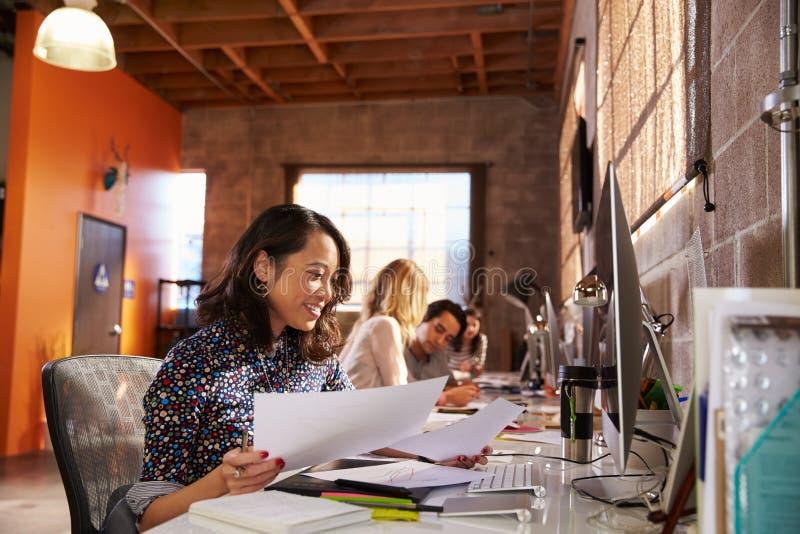 Команда дизайнеров работая на столах в современном офисе стоковая фотография rf