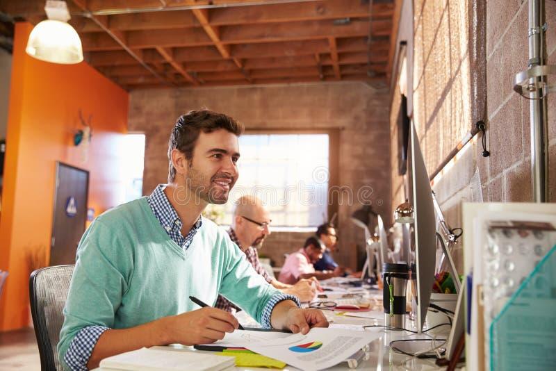 Команда дизайнеров работая на столах в современном офисе стоковая фотография