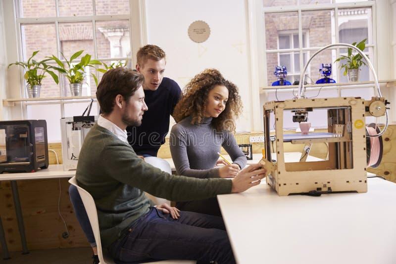 Команда дизайнеров работая с принтером 3D в студии дизайна стоковые фото